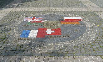 Bild von Heilbronn: Partnerstädte Heilbronns mit Flaggen von deren Ländern, Entfernungen dorthin und Heilbronner Stadtwappen; im Boden vor dem Rathaus